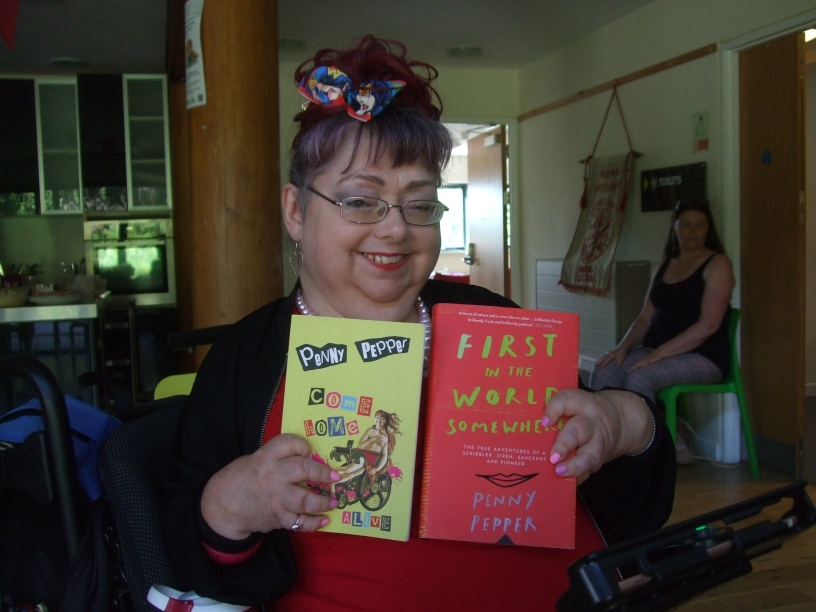 "Penny Pepper with her book of poetry and her memoir, ""First in the world somewhere"""