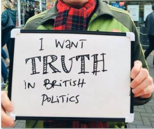 Man holds up placard saying 'I want TRUTH in British politics'