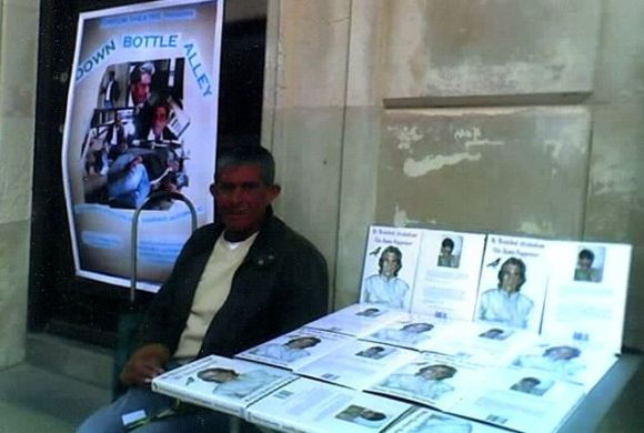"Brian on a street corner with his books on a table, and a poster of the play about his life, ""Down Bottle Alley"""