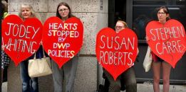 Activists with 'broken heart' placards commemorating those killed by DWP austerity