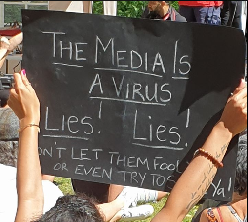 "Protestors' banner - ""The Media Is A Virus"""