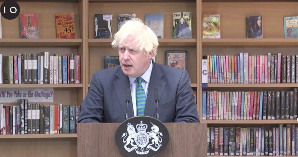 Boris Johnson addresses a school from a lecturn in a library. Clearly, a librarian went to a lot of bother to have relevant books - eg Farenheit 451 - on the shelves behind him.