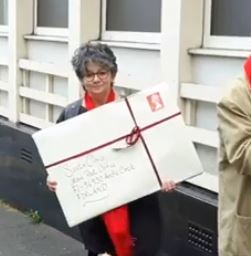 Julia delivers a LARGE letter at the demonstration after the public meeting to save the post office.