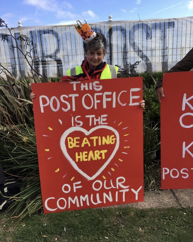 Julia wearing one of a set of crowns made by one of the campaigners - to emphasise the community's campaign to save the integrity of St Leonards Crown Post Office. Her placard: This PO is the beating heart of our community